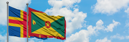 Aland Islands and Grenada flag waving in the wind against white cloudy blue sky together. Diplomacy concept, international relations.
