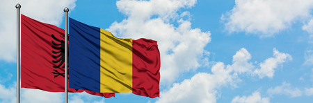 Albania and Romania flag waving in the wind against white cloudy blue sky together. Diplomacy concept, international relations.