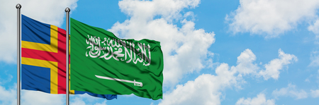 Aland Islands and Saudi Arabia flag waving in the wind against white cloudy blue sky together. Diplomacy concept, international relations. Banque d'images