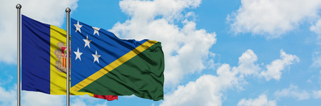 Andorra and Solomon Islands flag waving in the wind against white cloudy blue sky together. Diplomacy concept, international relations.