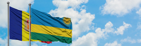 Andorra and Rwanda flag waving in the wind against white cloudy blue sky together. Diplomacy concept, international relations. Foto de archivo