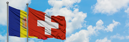 Andorra and Switzerland flag waving in the wind against white cloudy blue sky together. Diplomacy concept, international relations.