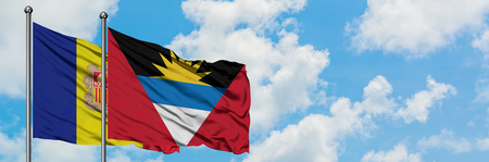 Andorra and Antigua and Barbuda flag waving in the wind against white cloudy blue sky together. Diplomacy concept, international relations.