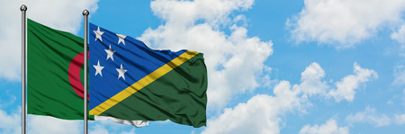 Algeria and Solomon Islands flag waving in the wind against white cloudy blue sky together. Diplomacy concept, international relations.