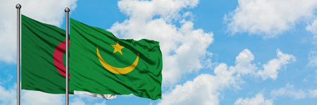 Algeria and Mauritania flag waving in the wind against white cloudy blue sky together. Diplomacy concept, international relations. Фото со стока