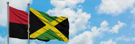 Angola and Jamaica flag waving in the wind against white cloudy blue sky together. Diplomacy concept, international relations.