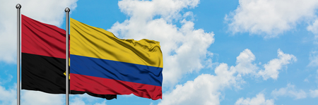 Angola and Colombia flag waving in the wind against white cloudy blue sky together. Diplomacy concept, international relations.