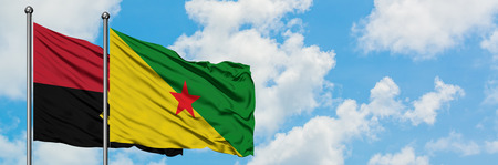 Angola and French Guiana flag waving in the wind against white cloudy blue sky together. Diplomacy concept, international relations.
