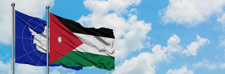 Antarctica and Jordan flag waving in the wind against white cloudy blue sky together. Diplomacy concept, international relations.