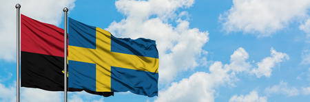 Angola and Sweden flag waving in the wind against white cloudy blue sky together. Diplomacy concept, international relations. Stock Photo