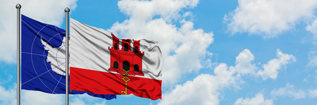 Antarctica and Gibraltar flag waving in the wind against white cloudy blue sky together. Diplomacy concept, international relations.