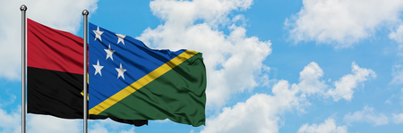 Angola and Solomon Islands flag waving in the wind against white cloudy blue sky together. Diplomacy concept, international relations. Stok Fotoğraf