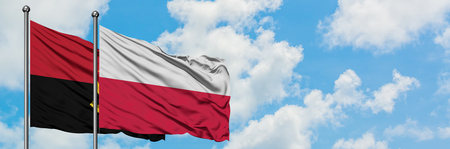 Angola and Poland flag waving in the wind against white cloudy blue sky together. Diplomacy concept, international relations.