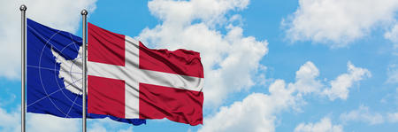 Antarctica and Denmark flag waving in the wind against white cloudy blue sky together. Diplomacy concept, international relations.