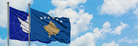 Antarctica and Kosovo flag waving in the wind against white cloudy blue sky together. Diplomacy concept, international relations.