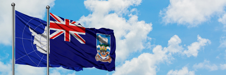 Antarctica and Falkland Islands flag waving in the wind against white cloudy blue sky together. Diplomacy concept, international relations.