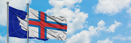 Antarctica and Faroe Islands flag waving in the wind against white cloudy blue sky together. Diplomacy concept, international relations.
