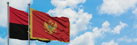 Angola and Montenegro flag waving in the wind against white cloudy blue sky together. Diplomacy concept, international relations.