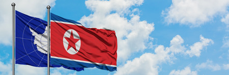 Antarctica and North Korea flag waving in the wind against white cloudy blue sky together. Diplomacy concept, international relations. Stock Photo