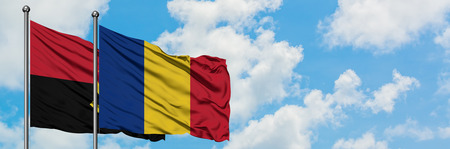 Angola and Romania flag waving in the wind against white cloudy blue sky together. Diplomacy concept, international relations.