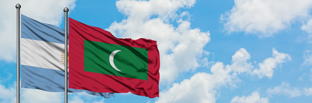 Argentina and Maldives flag waving in the wind against white cloudy blue sky together. Diplomacy concept, international relations. Stock Photo