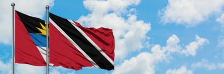 Antigua and Barbuda with Trinidad And Tobago flag waving in the wind against white cloudy blue sky together. Diplomacy concept, international relations.
