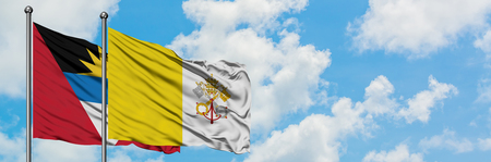 Antigua and Barbuda with Vatican City flag waving in the wind against white cloudy blue sky together. Diplomacy concept, international relations. 版權商用圖片