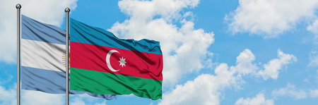 Argentina and Azerbaijan flag waving in the wind against white cloudy blue sky together. Diplomacy concept, international relations. Stock Photo