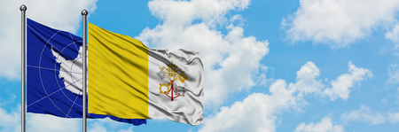Antarctica and Vatican City flag waving in the wind against white cloudy blue sky together. Diplomacy concept, international relations.