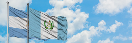 Argentina and Guatemala flag waving in the wind against white cloudy blue sky together. Diplomacy concept, international relations.