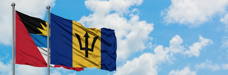 Antigua and Barbuda with Barbados flag waving in the wind against white cloudy blue sky together. Diplomacy concept, international relations.