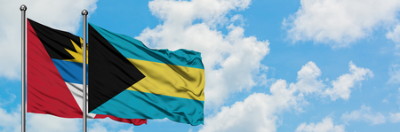 Antigua and Barbuda with Bahamas flag waving in the wind against white cloudy blue sky together. Diplomacy concept, international relations.