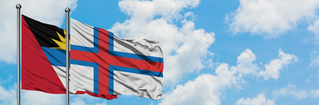 Antigua and Barbuda with Faroe Islands flag waving in the wind against white cloudy blue sky together. Diplomacy concept, international relations. Stock Photo