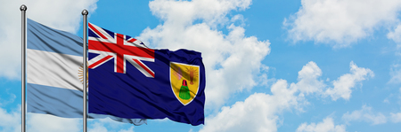 Argentina and Turks And Caicos Islands flag waving in the wind against white cloudy blue sky together. Diplomacy concept, international relations.