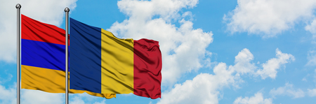 Armenia and Romania flag waving in the wind against white cloudy blue sky together. Diplomacy concept, international relations.