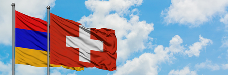 Armenia and Switzerland flag waving in the wind against white cloudy blue sky together. Diplomacy concept, international relations.