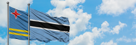 Aruba and Botswana flag waving in the wind against white cloudy blue sky together. Diplomacy concept, international relations. Stock Photo
