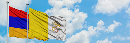 Armenia and Vatican City flag waving in the wind against white cloudy blue sky together. Diplomacy concept, international relations. 版權商用圖片