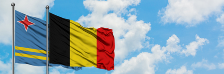 Aruba and Belgium flag waving in the wind against white cloudy blue sky together. Diplomacy concept, international relations. Stock Photo