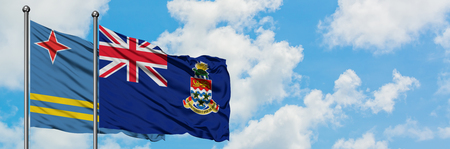 Aruba and Cayman Islands flag waving in the wind against white cloudy blue sky together. Diplomacy concept, international relations. Stock Photo