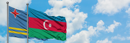 Aruba and Azerbaijan flag waving in the wind against white cloudy blue sky together. Diplomacy concept, international relations. Stock Photo