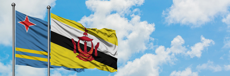 Aruba and Brunei flag waving in the wind against white cloudy blue sky together. Diplomacy concept, international relations. Stock Photo
