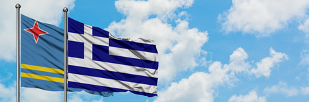 Aruba and Greece flag waving in the wind against white cloudy blue sky together. Diplomacy concept, international relations. Stock Photo