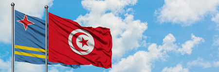 Aruba and Tunisia flag waving in the wind against white cloudy blue sky together. Diplomacy concept, international relations.