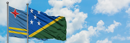 Aruba and Solomon Islands flag waving in the wind against white cloudy blue sky together. Diplomacy concept, international relations.