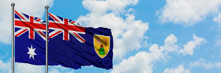 Australia and Turks And Caicos Islands flag waving in the wind against white cloudy blue sky together. Diplomacy concept, international relations.