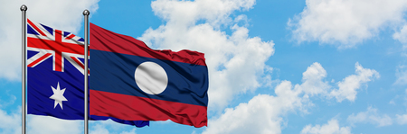 Australia and Laos flag waving in the wind against white cloudy blue sky together. Diplomacy concept, international relations. Banco de Imagens