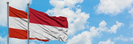 Austria and Indonesia flag waving in the wind against white cloudy blue sky together. Diplomacy concept, international relations.