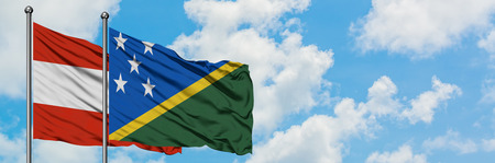 Austria and Solomon Islands flag waving in the wind against white cloudy blue sky together. Diplomacy concept, international relations.