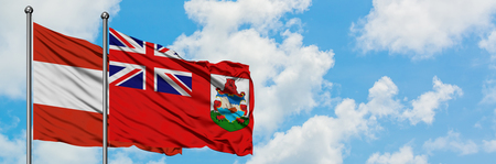 Austria and Bermuda flag waving in the wind against white cloudy blue sky together. Diplomacy concept, international relations. Imagens